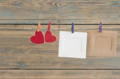 leere sofortige Fotos, die an der Wäscheleine mit rotem Herzen hängen Stockfoto