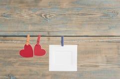 leere sofortige Fotos, die an der Wäscheleine mit rotem Herzen hängen Stockfotos