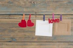 leere sofortige Fotos, die an der Wäscheleine mit rotem Herzen hängen Lizenzfreies Stockfoto