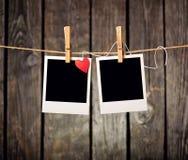 Leere sofortige Fotos und kleines rotes Papierherz Stockfotografie