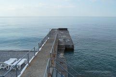 Leere Sonnenruhesessel durch das Meer früh morgens, Ruhe, Sonnenaufgang lizenzfreies stockfoto