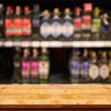 Leere Spitze des Holztischs mit unscharfer Gegenstange und Flaschen B stockfoto