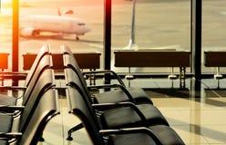 Leere Stühle im Abfahrtaufenthaltsraum des Flughafens Stockbild
