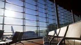 Leere Stühle im sonnenbeschienen Flughafenabfertigungsgebäude, Flugzeug, das hinter dem Fenster, besteigend steht stock video