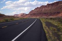 Leere Straße, die weg in die schönen, roten Berge von Nort führt Lizenzfreie Stockbilder