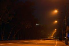 Leere Straße am frühen Morgen vor der Dämmerung eingehüllt in Nebel illum Lizenzfreies Stockfoto