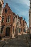 Leere Straße mit Backsteinbauten in typischer Art Flanders's und blauem Himmel in Brügge Lizenzfreies Stockfoto