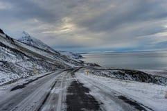 Leere Straße mit isländischer Landschaft während der Sünde der Abend herein Stockfotografie