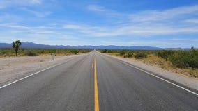 Leere Straße mitten in Wüste Stockfotos