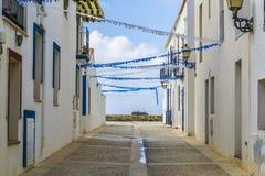 Leere Straße von weißen Häusern mit netter blauer Dekoration in Tabarca-Insel während der Feiertage Stockbilder