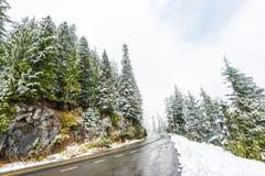 Leere Straße zum Berg mit Schnee umfasste Landschaft im Winter Lizenzfreie Stockbilder