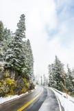 Leere Straße zum Berg mit Schnee umfasste Landschaft im Winter Lizenzfreie Stockfotos