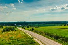 Leere Straße zwischen den Feldern, die zu das Dorf führen Stockbilder