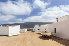 Leere Stra?e mit Sand und wei?e H?user in Caleta de Sebo auf dem Insel La Graciosa lizenzfreie stockbilder