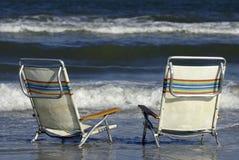 Leere Strand-Stühle in der Brandung Stockfotografie