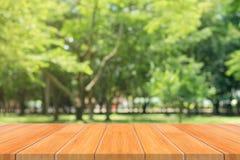 Leere Tabelle des hölzernen Brettes vor unscharfem Hintergrund Braune hölzerne Tabelle der Perspektive über Unschärfebäumen im Wa Lizenzfreie Stockfotografie