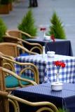 Leere Tabellen auf der Straße mit Rosen auf ihnen außerhalb eines Kaffeestabes oder -gaststätte. Stockfotografie