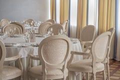 Leere Tabellen und Stühle mit Gläsern und Platten stellten in Restaurant ein Stockfoto