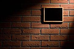 Leere Tafel, die an der Backsteinmauer hängt Stockbilder