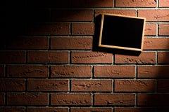 Leere Tafel, die an der Backsteinmauer hängt Lizenzfreies Stockfoto