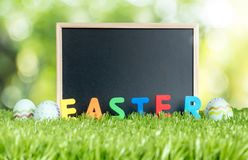 Leere Tafel mit buntem Ostern-Wort und -farbe ärgert auf gre Lizenzfreies Stockfoto
