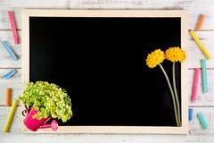 Leere Tafel und gelbe Plastikblumen auf Holztisch temperatur stockfoto