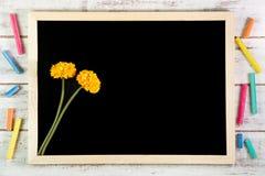 Leere Tafel und gelbe Plastikblumen auf Holztisch temperatur lizenzfreie stockfotos