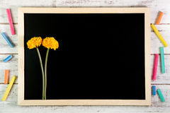 Leere Tafel und gelbe Plastikblumen auf Holztisch temperatur lizenzfreies stockbild