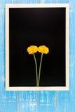 Leere Tafel und gelbe Plastikblumen auf Holztisch temperatur stockfotos