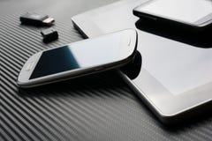 Leere Telefone mit der Reflexion, die auf Geschäfts-Tablet neben einem USB-Blitz-Antrieb über einem Kohlenstoff-Hintergrund liegt Stockfoto