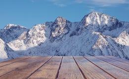 Leere Tischplatte gegen die Spitze eines schneebedeckten Berges Konzeptreise und -ferien in den Bergen im Winter stockfotografie