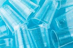 Leere transparente Wegwerfplastikgläser in den Wassertropfen auf blauem Hintergrund, Draufsicht Stockfotos