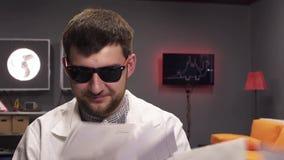 Leere Umschläge fallen auf netter junger Mannestragende Sonnenbrille und weißen Laborkittel stock video