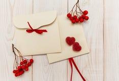 Leere Umschläge mit roter Eberesche und Streifen Jujube mit zwei rote Herzen Weiße hölzerne Tabelle Lizenzfreie Stockfotos