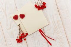 Leere Umschläge mit roter Eberesche und Streifen Jujube mit zwei rote Herzen Weiße hölzerne Tabelle Mokup mit leerem Raum Stockbild