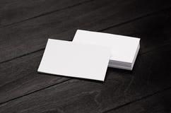 Leere Unternehmensidentitä5svisitenkarte und -stapel auf schwarzem stilvollem hölzernem Hintergrund mit Unschärfe, Schablone stockfotos