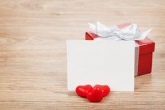 Leere Valentinsgrußgrußkarte, Geschenkbox und rote Süßigkeitsherzen Lizenzfreie Stockfotos