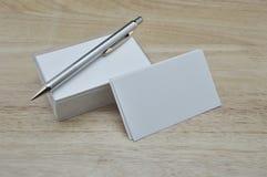Leere Visitenkarten und Bleistift auf Holztisch Stockbilder