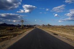 Leere Wüstenstraße, die zum Horizont ausdehnt Stockbild