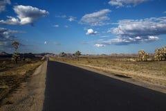 Leere Wüstenstraße, die zum Horizont ausdehnt Lizenzfreie Stockbilder