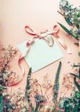 Leere Weißbuchkarte mit Band und Blumen auf Pastellhintergrund, Draufsicht Festliche Grußkarte Stockfotos