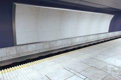 Leere weiße Anschlagtafel auf violetter Wand in der leeren U-Bahn Stockfotografie