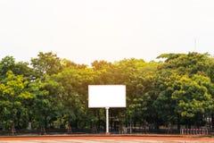 Leere weiße Anschlagtafel die Rückseite ist von den Bäumen voll Lizenzfreies Stockbild