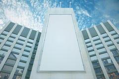 Leere weiße Anschlagtafel unter Wolkenkratzern mit blauem Himmel Lizenzfreie Stockfotografie