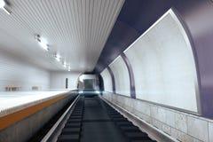 Leere weiße Anschlagtafeln auf violetter Wand in der leeren U-Bahn mit Zug Lizenzfreie Stockfotografie