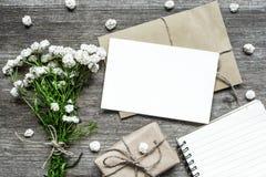Leere weiße Grußkarte mit Blumenstrauß der weißen Blumen und Umschlag mit Geschenkbox- und Papiernotizbuch Stockfotos