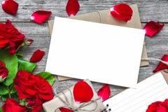 Leere weiße Grußkarte mit Rotrosen-Blumenblumenstrauß und Umschlag mit den Blumenblättern, gezeichnetem Notizbuch und Geschenkbox Stockbilder