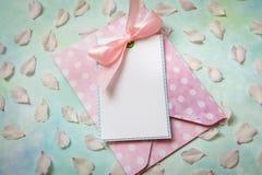 Leere weiße Grußkarte und -umschlag mit den Blumenblättern von Frühlingsblumen und -seil über rustikaler Tabelle mit Kopienraum S stockfotos