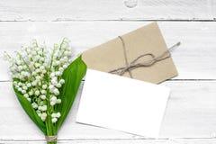 Leere weiße Grußkarte und -umschlag mit Frühlingsmaiglöckchen blüht stockfoto