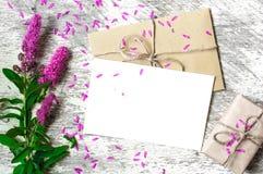 Leere weiße Grußkarte und -umschlag mit purpurroten Wildflowers und Weinlesegeschenkbox Stockfotos